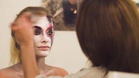 Dessin de maquilleur sur le visage modèle du ` s banque de vidéos