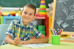 Dessin de petit garçon avec le crayon Photographie stock