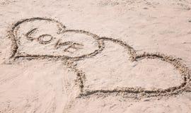 Dessin des coeurs avec le mot AMOUR sur le sable Photographie stock libre de droits