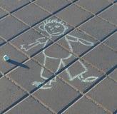 Dessin drôle d'un homme par la craie sur l'asphalte Image stock