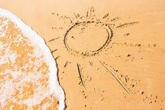 Dessin du soleil sur le fond de sable Images stock