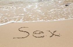 Dessin en sable par l'océan du mot de sexe Photos libres de droits