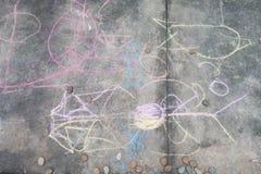 Dessin et coloration de petit garçon par la craie sur l'activité au sol d'art Photos libres de droits