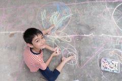 Dessin et coloration de petit garçon par la craie sur l'activité au sol d'art Images libres de droits