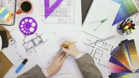 Dessin femelle d'architecte sur le modèle utilisant des règles La vue supérieure de la table avec des architectes prévoient banque de vidéos