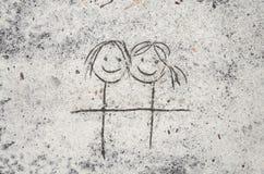 Dessin femelle de couples sur le fond de sable Photos stock