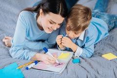 Dessin gai de mère et de fils dans un carnet Image stock