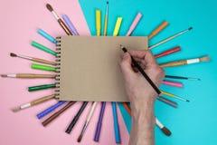 Dessin masculin de main, papier blanc et crayons color?s En stigmatisant la sc?ne de maquette de papeterie, masquez les objets po photos libres de droits