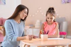 Dessin mignon d'enfant à la table avec sa mère en jouant la chambre Photographie stock
