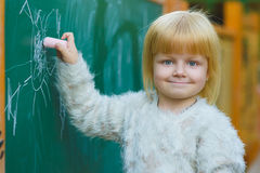 Dessin mignon d'enfant avec la craie sur le tableau noir extérieur Image stock