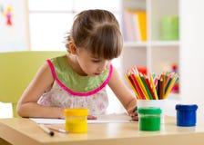 Dessin mignon de fille d'enfant d'élève du cours préparatoire avec des crayons à la maison Photo stock