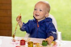 Dessin mignon de petit garçon sur la table blanche avec la gouache images libres de droits