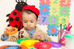 Dessin noir de garçon d'afro-américain avec les crayons colorés dans l'école maternelle dans le jardin d'enfants Photographie stock