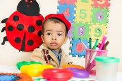 Dessin noir de garçon d'afro-américain avec les crayons colorés dans l'école maternelle dans le jardin d'enfants Photo stock