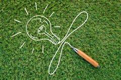 Dessin pointu de crayon et d'ampoule sur le fond d'herbe verte jpg Photo stock