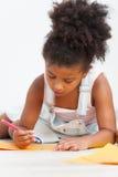 Dessin préscolaire mignon de fille d'enfant sur le plancher photos libres de droits