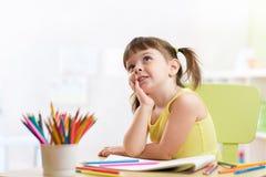 Dessin rêveur de fille d'enfant avec des crayons de couleur Photo libre de droits
