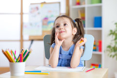 Dessin rêveur de fille d'enfant avec des crayons de couleur Photos libres de droits