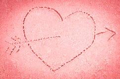 Dessin rouge de coeur sur le sable Images libres de droits