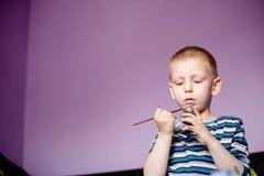 Dessin sérieux de petit garçon avec des couleurs d'eau Photo libre de droits