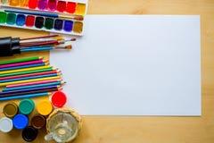 Dessinant fournit des brosses, crayon, aquarelle, la gouache, papier sur le fond en bois Images stock