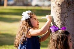 Dessinant quelque chose assez sur un arbre Photo libre de droits
