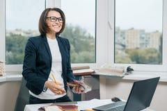Dessinateur d'intérieurs de décorateur féminin sur le lieu de travail avec des échantillons de tissu, ordinateur portable Femelle images libres de droits