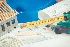 Dessins électriques, outils de travail et accessoires, petite maison et dollar de devises, concept à la maison de construction de Photographie stock