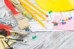 Dessins, casque jaune et différents outils de construction images libres de droits