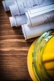 Dessins de construction de lunettes de sécurité et casque de bâtiment sur le bois Photos stock