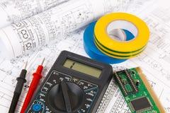 Dessins imprimés des circuits électriques, du multimètre numérique, du conseil électronique et de la bande d'isolation photo stock