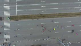 Dessus aérien abattu de beaucoup de personnes sportives au marathon courant sur la route urbaine banque de vidéos