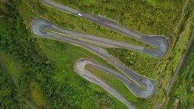 Dessus aérien en bas de l'entraînement de voitures sur le zigzag enroulant la route serpentine, caméra verrouillée banque de vidéos