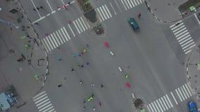Dessus aérien en bas de tir d'intersection de route urbaine avec des personnes courant au marathon banque de vidéos