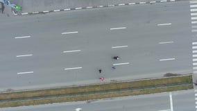 Dessus aérien en bas de tir du groupe des coureurs et du cycliste au marathon sur la route urbaine clips vidéos