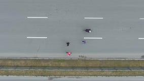 Dessus aérien en bas de tir du groupe des coureurs et du cycliste au marathon de ville banque de vidéos