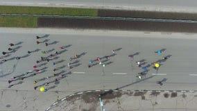 Dessus aérien en bas du tir des personnes sportives au marathon courant sur la route urbaine banque de vidéos