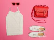 Dessus blanc de dentelle, sac à main rouge, espadrilles blanches et verres roses Fond rose lumineux Images libres de droits