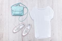 Dessus blanc, espadrilles blanches et un sac en bon état concept à la mode Fond en bois Photographie stock libre de droits