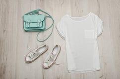 Dessus blanc, espadrilles blanches et un sac en bon état concept à la mode Fond en bois Photo stock