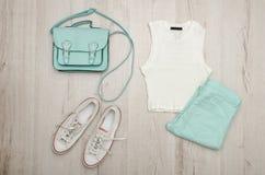 Dessus blanc, jeans de couleur menthe, espadrilles blanches et sac à main concept à la mode Fond en bois Images libres de droits