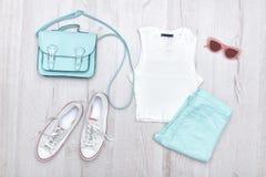 Dessus blanc, jeans de couleur menthe, espadrilles blanches et sac à main concept à la mode Fond en bois Photographie stock libre de droits