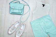 Dessus blanc, jeans de couleur menthe, espadrilles blanches et sac à main concept à la mode Fond en bois Photos libres de droits