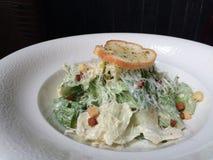 Dessus classique fait maison frais en gros plan de salade de César avec le lard et le pain à l'ail images stock