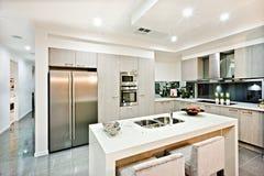 Dessus de comptoir de cuisine moderne avec un réfrigérateur et un office Photo stock