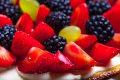 Dessus de gâteau fait maison de biscuit avec de la crème et des baies sur le CCB noir images libres de droits