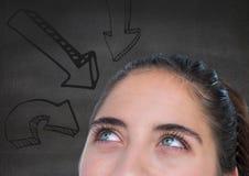 Dessus de la tête de la femme regardant les flèches de haut en bas contre le mur gris Image libre de droits