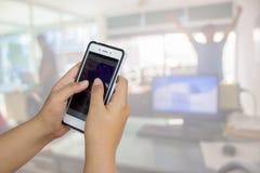 Dessus de main de Smartphone et bureau de tache floue OE abstrait de fond de tache floue Photo stock