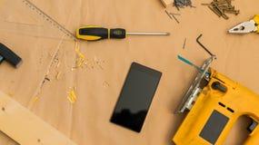 Dessus de table de bureau d'atelier de bricoleur de charpentier avec le téléphone de samrt image libre de droits