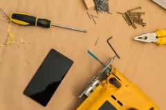 Dessus de table de bureau d'atelier de bricoleur de charpentier avec le téléphone intelligent images stock